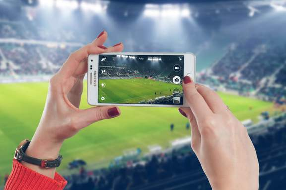 close-up of a woman taking a picture from a football stadium with a samsung smartphone