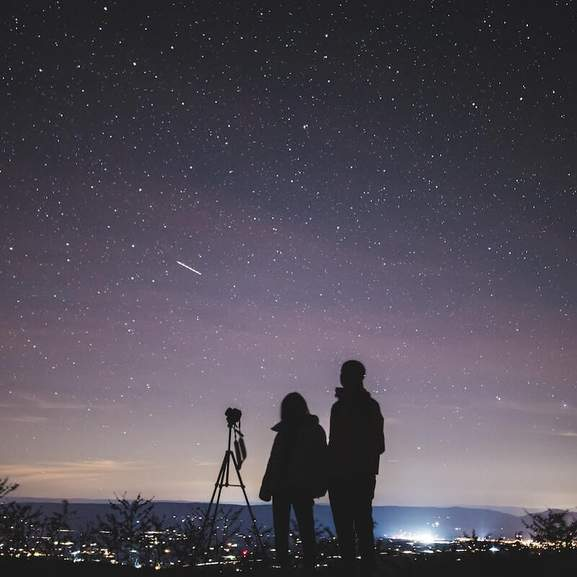 Two people by telescope stargazing