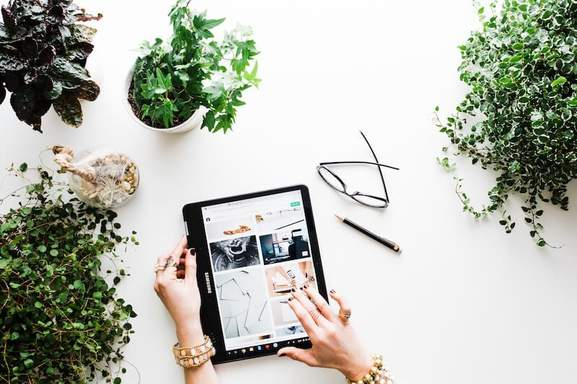 close-up of woman's hands using a samsung galaxy tab while sitting at a white table and plants standing nearby