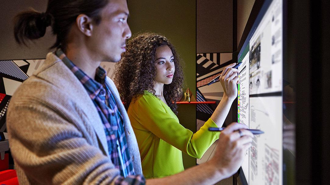 Man and woman using Microsoft Surface Hub