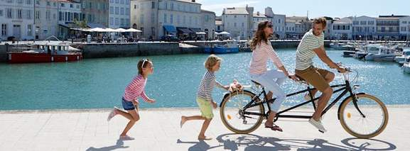 a family near the port with a tandem bike in stripe t-shirts