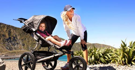 mom is taking a walk with baby girl in a pram at a beach side