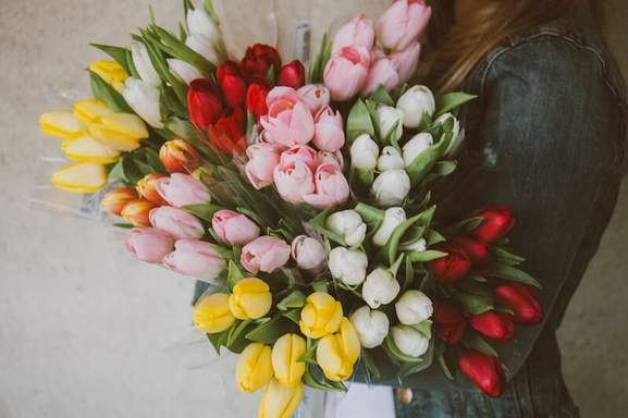 a woman in a jeans jacket carrying multiple bouquets of colorful tulips