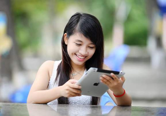 smiling asian woman is looking at an ipad
