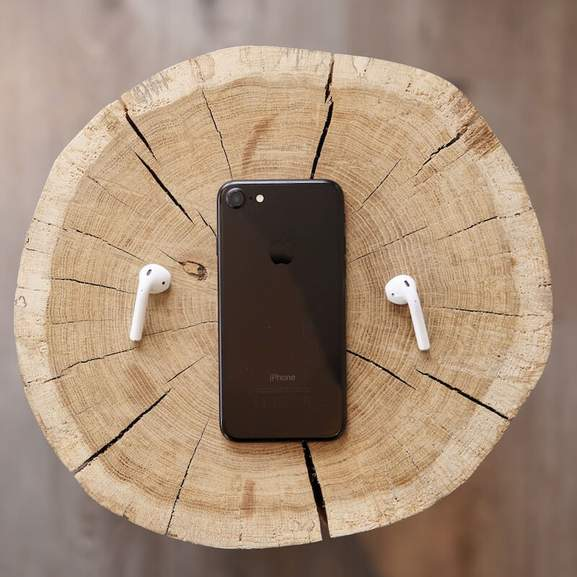 Apple Airpods next to black iPhone on wooden stump
