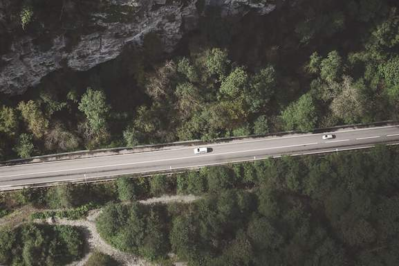 drone shot of two cars on the highway surrounded by hills