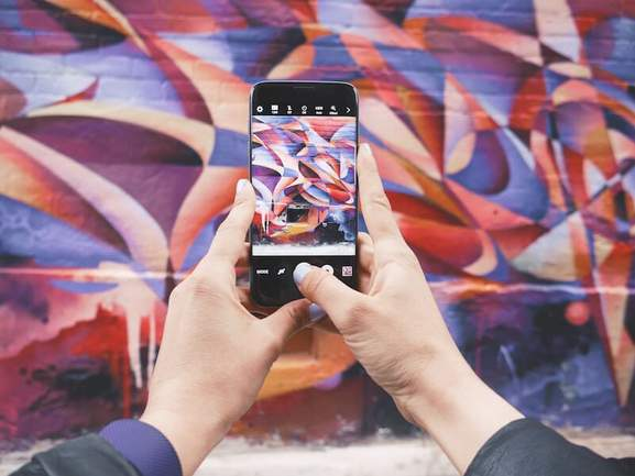 hands holding iphone taking photo of abstract colorful graffiti art