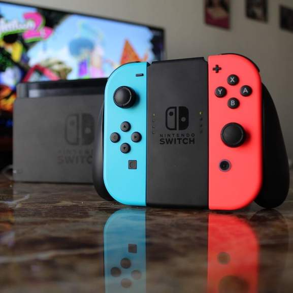 Red and blue Nintendo Switch Joy-Cons in front of Switch