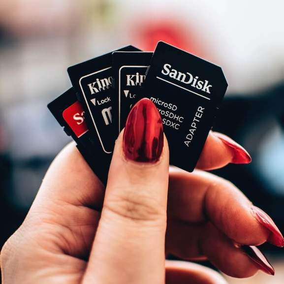 2 SanDisk Micro SD Card Adapters and 2 Kingston Micro SD Card adapters behind thumb with red nail