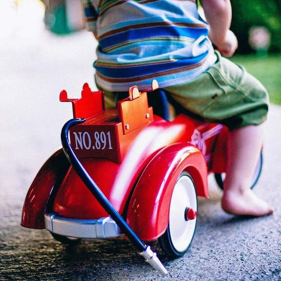 Toddler on red tricycle