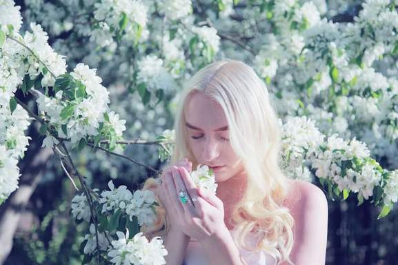 young woman enjoying the lovely spring blossoms that are smelling like perfume