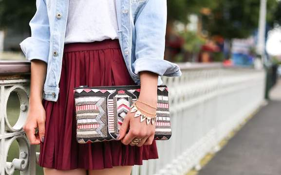 woman in a red skirt, jeans shirt, and bracelets holds a patterned clutch