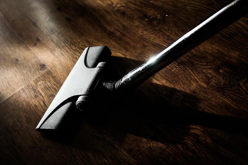 vacuum cleaner used on a dark wooden floor