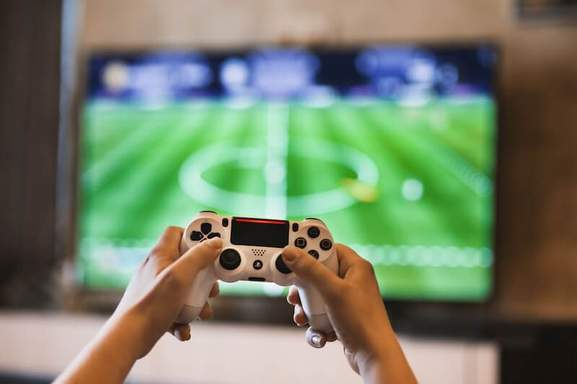 person holding playstation game controller in front of a blurred tv