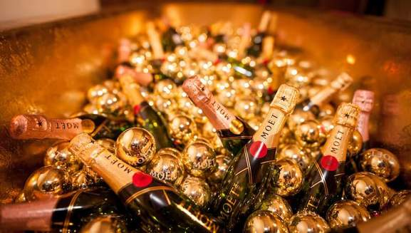 lots of moet champagne bottles lying in a big bowl