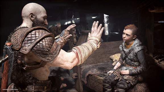kratos is holding up his arms in front of his son atreus who is sitting on a bed