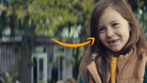 girl with missing teeth smiling next to an amazon sign