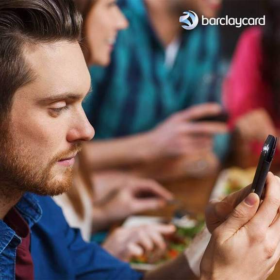 a guy is looking on his mobile phone and barclaycard branding