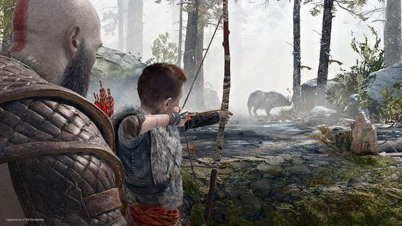 kratos is showing his son atreus to hunt down a boar with a bow in the woods