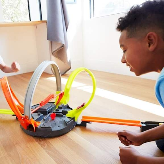 Kid playing with Hot wheels cars on hot wheels track