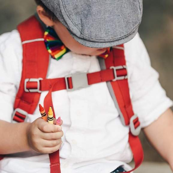 Boy wearing red bag in hat, bow tie and white shirt holding crayons