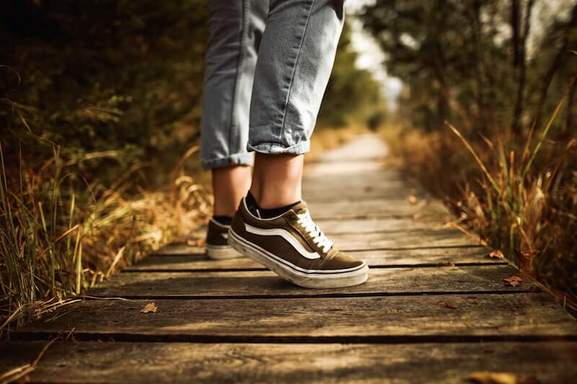 female wearing vans on a small way with wooden planks