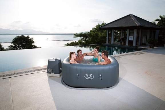 4 people sitting in a lay-z spa hot tub at the seaside