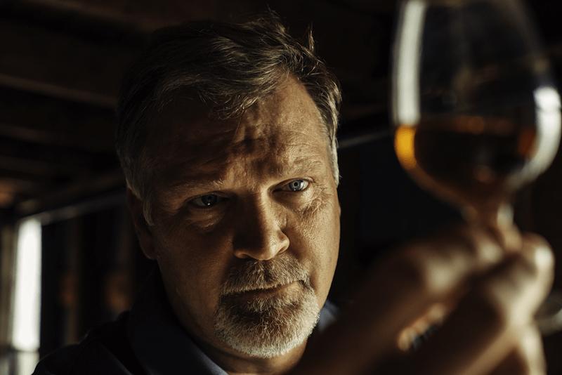 man diagnosing a distillery glass of jack daniels whisky