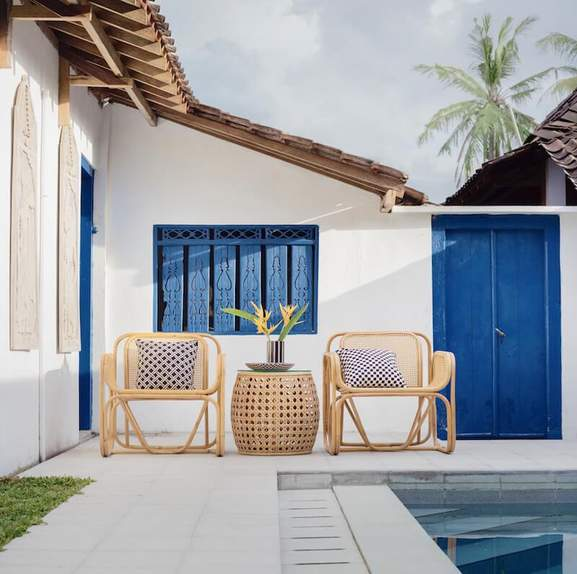 outside pool area with rattan armchairs