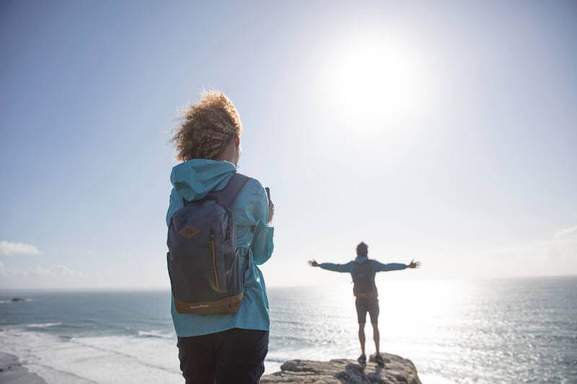 man and woman in decathlon gear are standing on a summit looking over the sea seen from behind