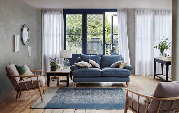 stylish living room with blue sofa, carpet and cosy seats