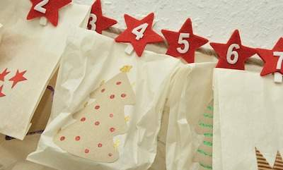 White advent calendar with red stars on the wall
