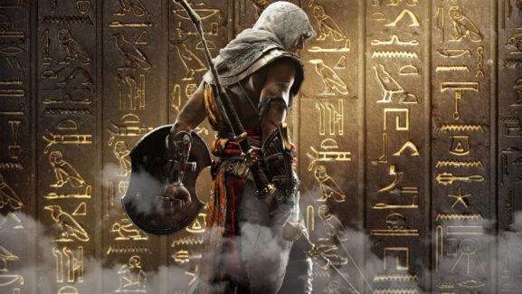 bayek with arms in front of a wall with egyptian hieroglyphs