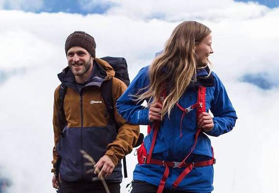 man and woman with hiking clothes and equipment walking under a cloudy sky