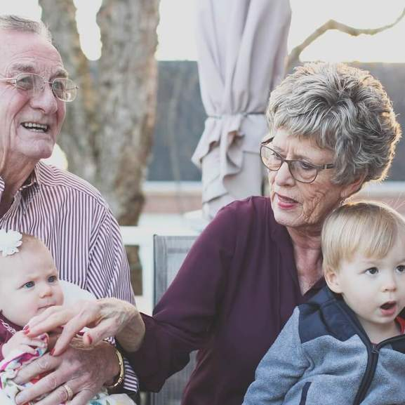 Grandparents showing affection to grandchildren whilst sitting on laps