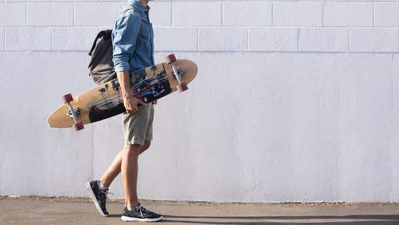 skater guy in front of a white brick wall in california