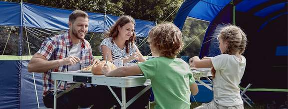 parents and children sitting at a camping table eating