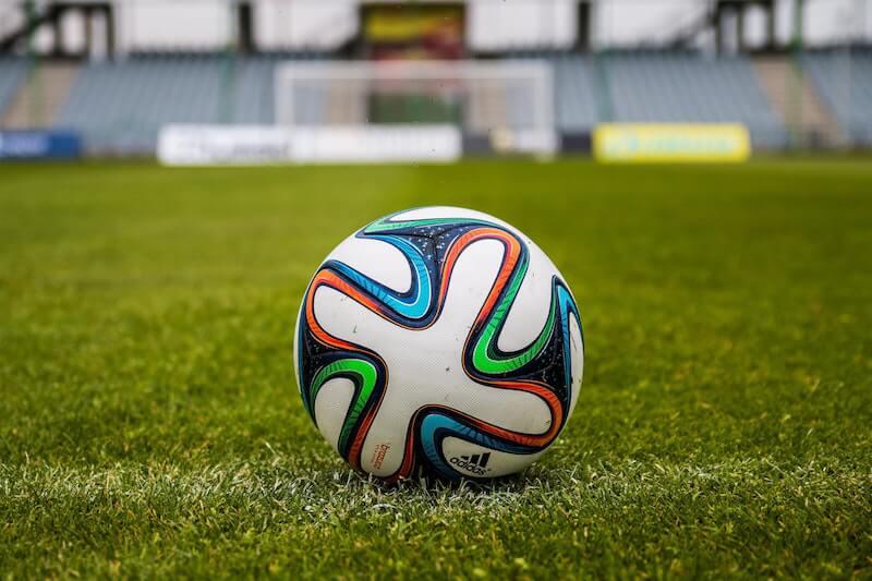 adidas football lying on the lawn of an empty football stadium
