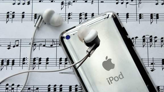 ipod with earpods and written music in the background