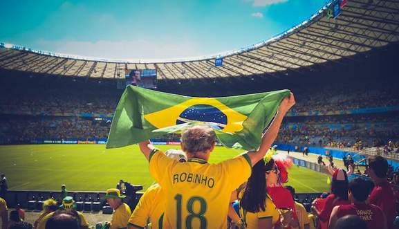 audience in a football stadium in brazil focussing on an older man with thinning hair wearing a robinho trikot and a brazil flag