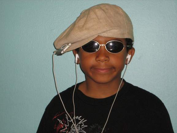 child listening to his ipod shuffle wearing cool glasses and a hat