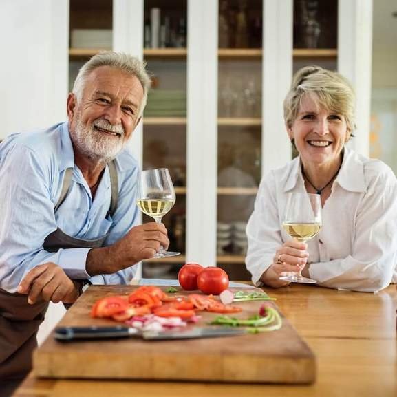 Two Grandparents smiling, drinking wine whilst cooking