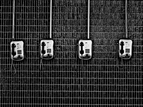 4 phones hanging on a tiled wall