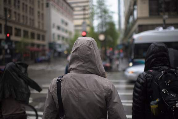 jacket covering 3 people from rain in a town(