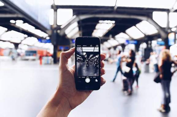 adult hand is taking a picture on a train station with his smartphone