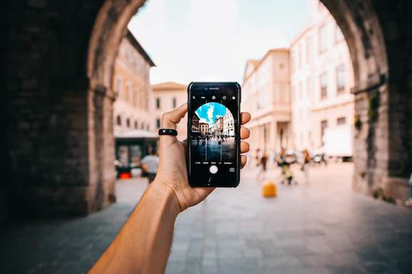 person holding black android smartphone making a picture of the architecture in an old town