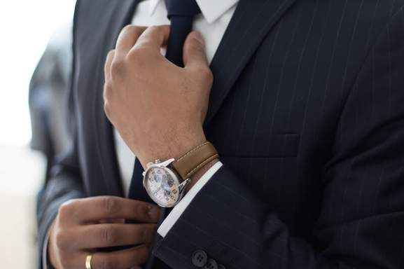 close-up of a businessman's hands with a watch adjusting his tie