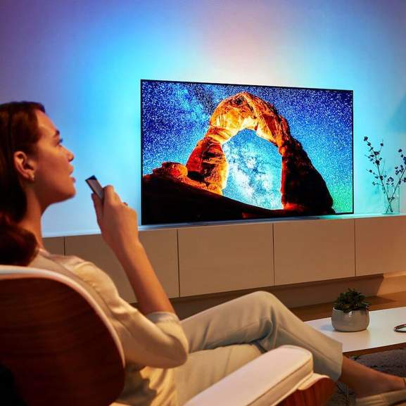 Woman using remote control to control Philips TV with ambilight