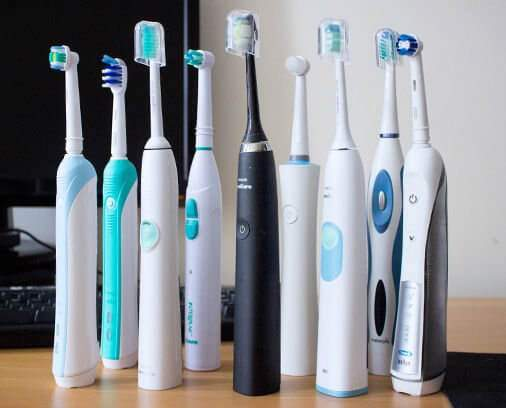 electric toothbrushes from different brands standing on a desk