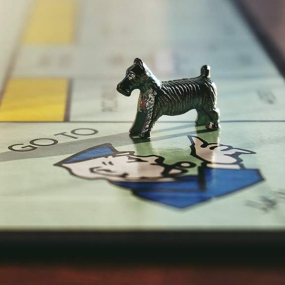 Dog monopoly piece on jail square next to red hotel